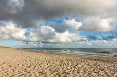 Beach sand with blue sky and dramatic clouds at coastline waterfront in soft evening sunset light. Hvidbjerg Strand, Blavand, North Sea, Denmark. Standard-Bild