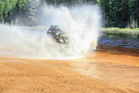 Man driving motocross ATV quad through splashing river lake water with high speed. Foy, Foyross Lake, Sudbury, Canada.