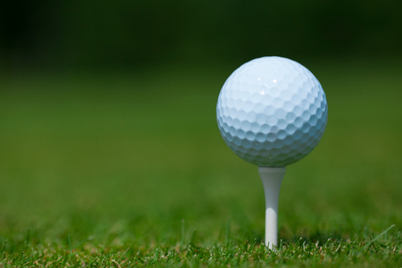 Golf ball: pelota de golf en una camiseta blanca con una hierba verde en el fondo. Tiro a nivel del suelo. Un mont�n de espacio para la copia o la cosecha a su gusto.