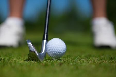 pelota de golf: un primer plano de una pelota de golf sobre un tee de golf blanco sobre hierba verde vibrante, con un jugador de golf Foto de archivo