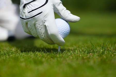 recreational pursuits: Getting ready to tee up a golf ball for a drive Stock Photo