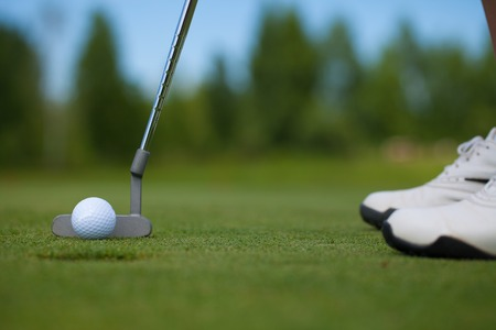 Photo of a golfer stepping up to his ball just inches from the hole, tapping in.