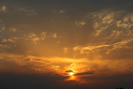 Beautiful sunset with bright orange sun, rays of light do through blue sky with clouds