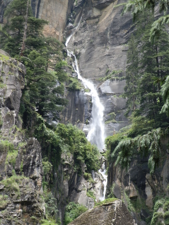 waterfall between two height rocks with forest and trees Banco de Imagens