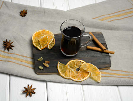 Glass glass of mulled wine on a gray napkin, with orange slices and anise stars.