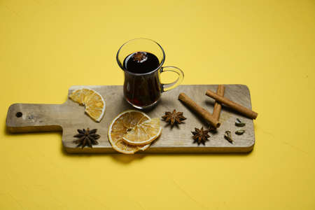 A glass of mulled wine on a wooden board with cinnamon sticks and dried orange. Top view