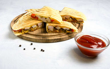 Quesadillas on a wooden plate on a white background.