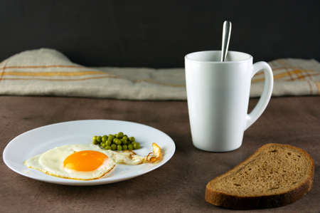 Traditional breakfast, fried eggs, bread, coffee in a white cup on a dark background.