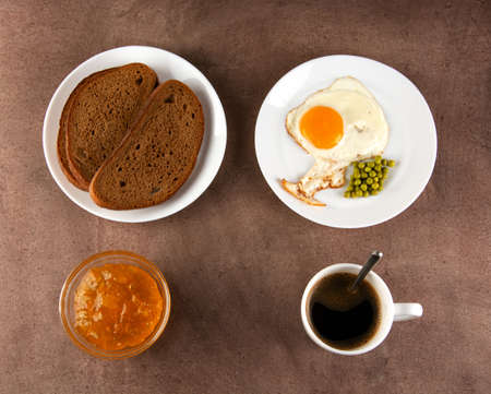 Classic breakfast: fried eggs, jam, bread, coffee in a white cup on a dark background.
