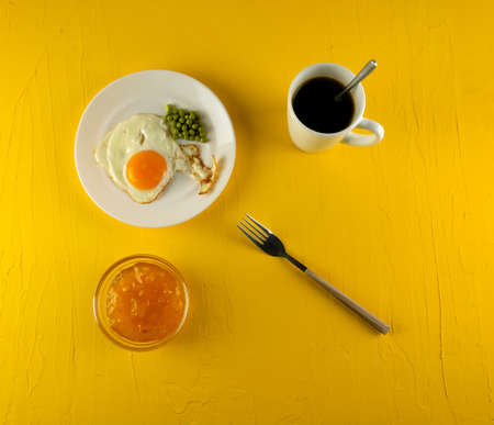 Breakfast: fried eggs, bread, coffee in a white cup on a yellow background.