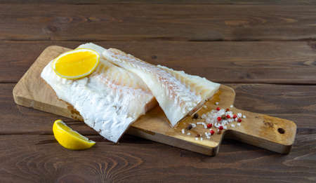 Cod on a wooden board with pepper, salt and lemon. Dark wooden background.