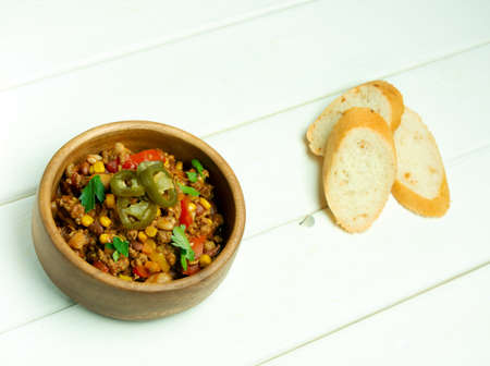 Bowl with chili con carne, white wooden background, slices of white bread