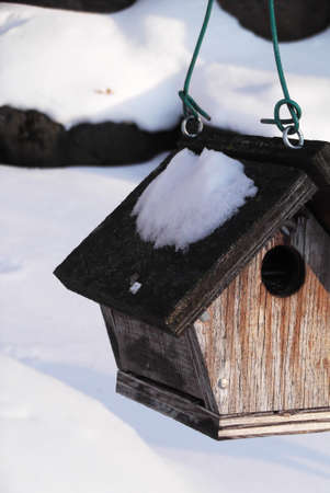 is covered: Hanging birdhouse covered in snow