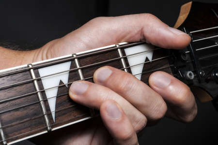 frets: Close up shot of a man with his fingers on the frets of a guitar
