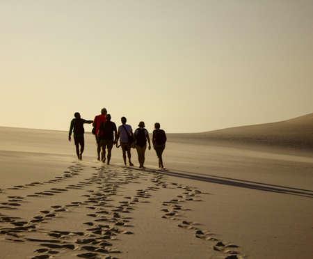 日没時に足跡を残して砂丘を歩いている人のグループ 写真素材 - 78892788