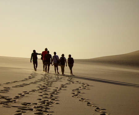 A group of people walking during sunset on dunes leaving footprints