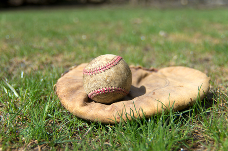 outfield: View of an old fashioned baseball glove and ball on a grass outfield