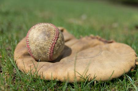A vintage baseball glove with a well worn ball on a grass field  photo