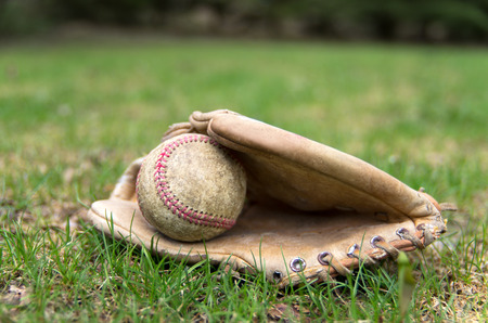 An old vintage baseball glove and ball lay on the early spring outfield Stock Photo - 27926937