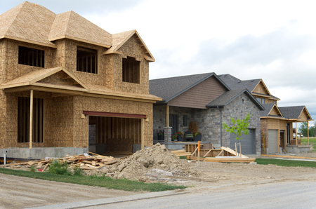 residential construction: View of a street with new houses under construction next to a recently completed one. Stock Photo