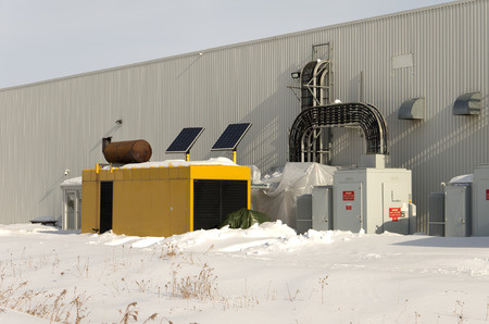 standby: Large industrial standby generator in winter. Stock Photo