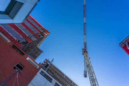 Bottom view of a crane and a work-in-progress building.