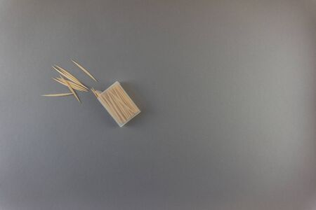 Messy arranged toothpicks with box on gray background