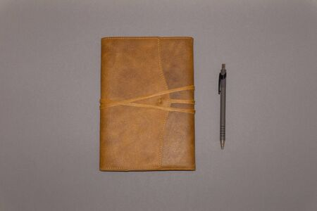 Leather notebook and pen on gray background