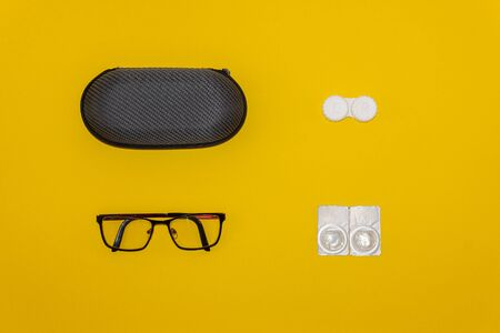Glasses, contact lenses and storage kits on yellow background