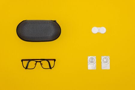 Glasses, contact lenses and storage cases on yellow background Фото со стока