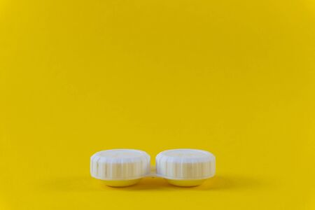 Contact lens storage case on yellow background Imagens