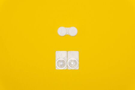 Contact lenses and lens storage case on yellow background Фото со стока