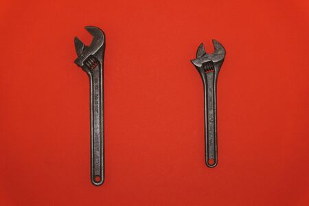 Old metal wrenches on a red background