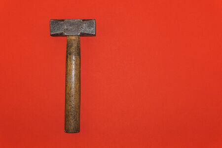 Brown handle hammer on a red background