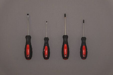 Red handle screwdrivers on a grey background 스톡 콘텐츠