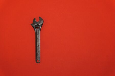 Old metal wrench on a red background 스톡 콘텐츠