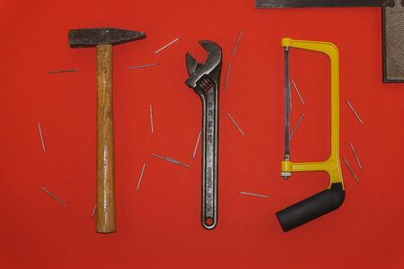 Metal hammer, wrench, and saw on red background with nails 스톡 콘텐츠
