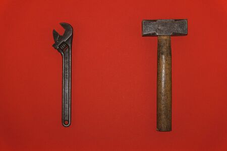 Old metal wrench and hammer on red background