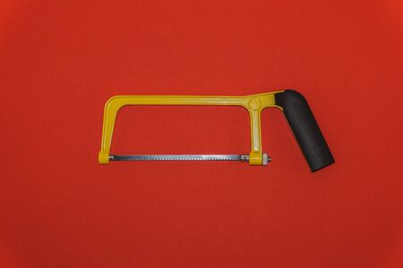 Yellow saw with black handle on red background