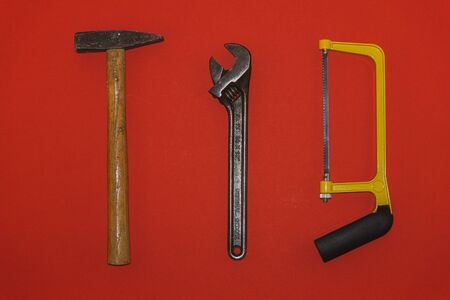 Metal hammer, wrench, and saw on red background 스톡 콘텐츠
