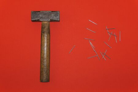 Brown handle hammer with nails on a red background