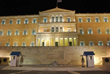 ATHENS, GREECE - AUGUST 6  Evzones sitting on guard in front of the Greek Parliament at night on August 6, 2013 in Athens, Greece