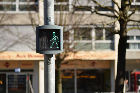 Green light for pedestrians in front of a blurry background in the street