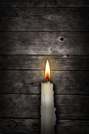 candle light: candle in front of old wooden planks Stock Photo