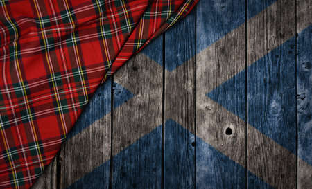 tartan textile on wooden background with scotland flag