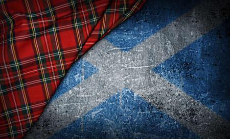 tartan textile on stone background with scotland flag Standard-Bild