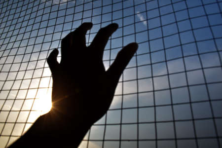 silhouette hand holding on iron net cage with blue sky and city background sunset Standard-Bild - 113935282