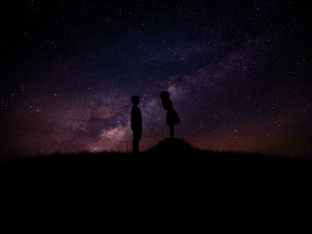 silhouette of man and woman over grass and hill with star milky way backgrounds, romantic valentine