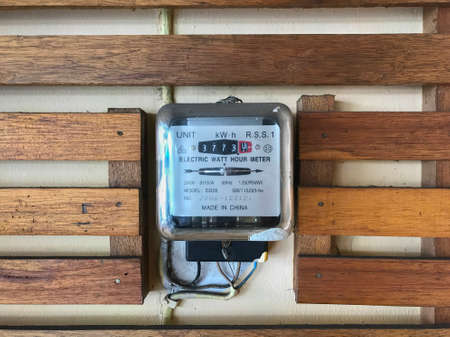 Watt hour electric meter measurement tool on wooden wall
