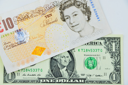 us dollars: british pounds and us dollars banknotes lie on each other
